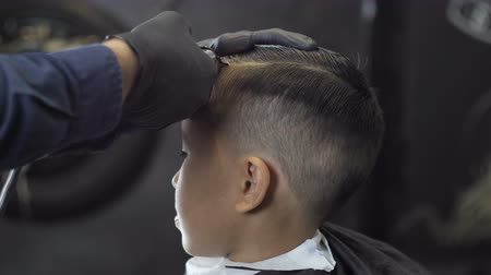 nape : Barber in black gloves shaves a parting on the head of an Asian child 60 fps