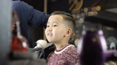 professionally : barber in black gloves makes a hairstyle for an Asian child, removes cut-off hair from the neck with a brush 60 fps