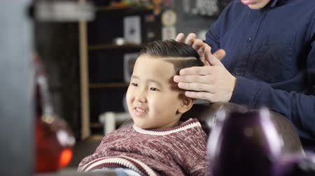 nape : Barber in black gloves makes a hairstyle for an Asian child, puts a gel on his hair 60 fps