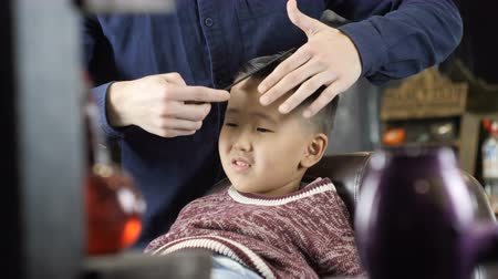 professionally : Barber in black gloves makes a hairstyle for an Asian child, combs hair, final moves 60 fps