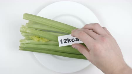 сельдерей : Amount of calories in celery, male hand puts a plate with the number of calories on a celery, top shot