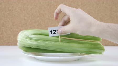 сельдерей : Amount of calories in celery, male hand puts a plate with the number of calories on a celery