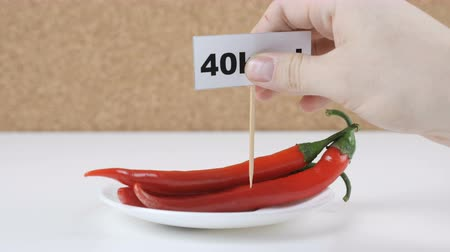besleme : Amount of calories in chili pepper, male hand puts a plate with the number of calories on a chili pepper Stok Video