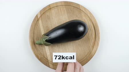 brinjal : Amount of calories in eggplant, male hand puts a plate with the number of calories on a eggplant, top shot Stock Footage