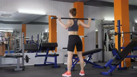 squatting : Young beautiful sporty girl squatting with a bar in a sport gym, back side view 60 fps
