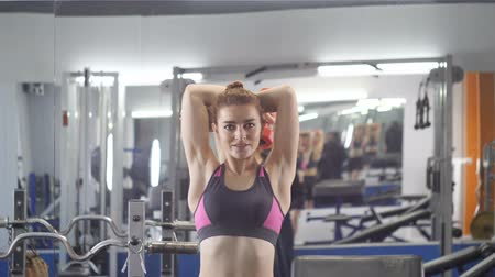 intenzivní : Sports young girl doing triceps extension exercise in gym. Woman holding free weight in hands behind head Front side view 60 fps