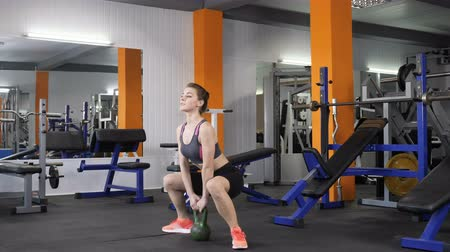 cross training : Young beautiful sporty girl doing weighted squats with a kettlebell in gym. 60 fps