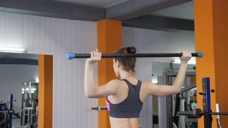 súlyzó : Young beautiful sporty girl lifting barbell bar in gym, shoulder exercise, back side view. 60 fps