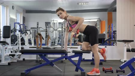 motivováni : Sports young girl leans on a sports bench pumps the muscles of the forearm, triceps with a dumbbell. 60 fps Dostupné videozáznamy