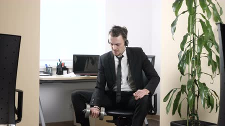 call out : Work out in the office, man in a suit does an exercise for the biceps while sitting in the office and speaking on the headset 60 fps
