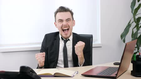 attainment : Young businessman in suit rejoices in victory while sitting in office 60 fps Stock Footage