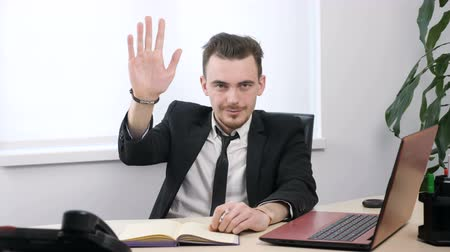 yours : Young businessman in suit showing hello sign and and waving his hand 60 fps