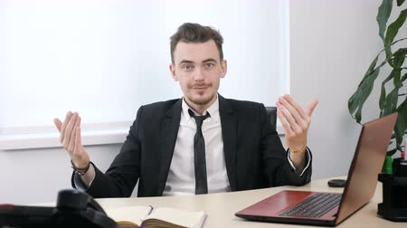 честолюбивый : Young businessman in suit sitting in office and showing come here or come on gesture 60 fps