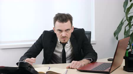 spite : Young angry businessman in suit is sitting in office and showing No by shaking head, gesture 60 fps Stock Footage