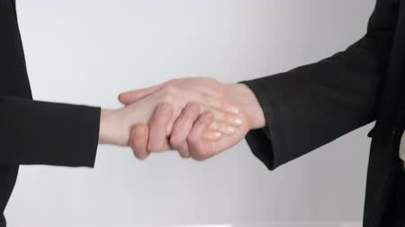 no hands : A young man and a girl in suits shake hands. Female and man hands shaking hands. Close up 60 fps Stock Footage