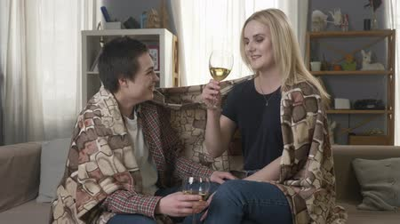 клетчатый : Two young, beautiful girls are sitting on the couch wrapping with warm plaid blanket, drinking wine and laughing, cosiness 60 fps