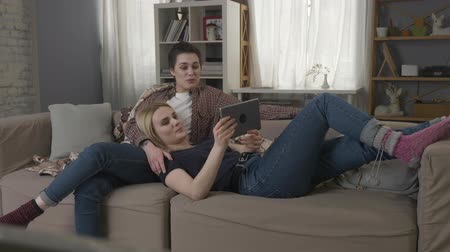 each other : Lesbian couple is resting on the couch, laughing and watching funny movie on tablet 60 fps