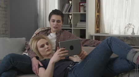 two gender : Lesbian couple is resting on the couch, using tablet computer, speaking, showing sign no by shaking head 60 fps Stock Footage
