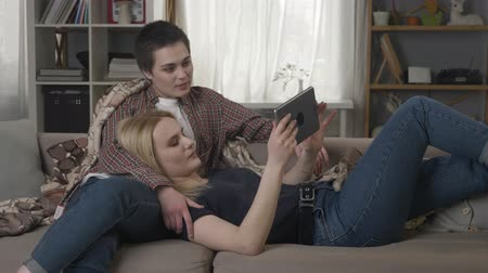 two gender : Lesbian couple is resting on the couch, using tablet computer, scrolling photos on tablet, holding hands, smiling, talking 60 fps