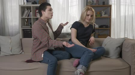 spite : Two young lesbian girls are sitting on the couch, quarreling, arguing, conflict, a girl with short hair apologizes to her partner 60 fps