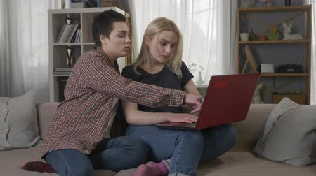 two gender : Two young lesbian girls are sitting on the couch, using a computer, scrolling the internet, shopping online 60 fps