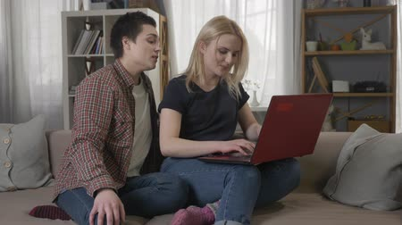 two gender : Two young lesbian girls are sitting on the couch, using a computer, scrolling the internet, shopping online, smiling, talking 60 fps