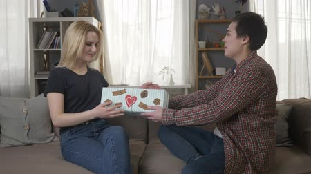 two gender : Two young lesbian girls are sitting on the couch, a girl with short hair gives a gift to her partner, love, a new year, a surprise. 60 fps Stock Footage