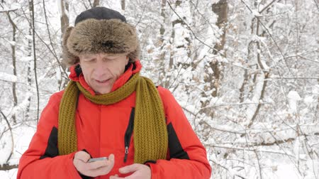 кампания : Elderly Caucasian man walks through the winter forest, trying to catch a signal on a smartphone. Thick dense thicket of trees and roots in in the snow-covered forest. Hike and travel concept 60 fps