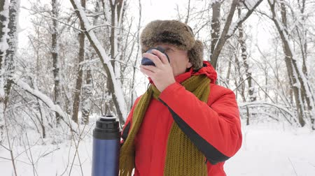bengala : Ederly European man drinking tea from a flask bottle in a snow-covered forest. Thick dense thicket of trees and roots in in the snow-covered forest. Hike and travel concept 60 fps