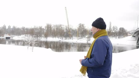 спринт : An elderly man runs a cross along the river in winter, sports, cardio. Healthy life concept. 60 fps Стоковые видеозаписи