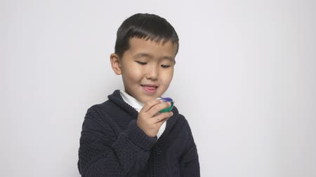 grotesque : Asian child holds washing powder pod in hand and licking lips. Looking into camera. Preparing to eat a capsule with detergent, washing powder pods challenge, internet meme. 60 fps