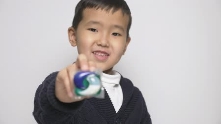 grotesque : Smiling Asian child giving a washing powder pod to the camera. Preparing to eat a capsule with detergent, washing powder pods challenge, internet meme. focus pull 60 fps