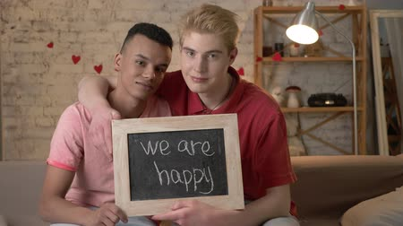 social inequality : A sad international gay couple is sitting on the couch and holding a sign. We are not happy. Look at the camera. Home comfort on the background. 60 fps