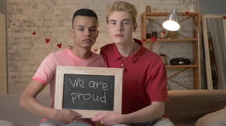 oppression : A sad international gay couple is sitting on the couch and holding a sign. We are proud. Look at the camera. Home comfort on the background. 60 fps Stock Footage