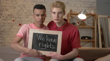 oppression : A sad international gay couple is sitting on the couch and holding a sign. We have rights. Look at the camera. Home comfort on the background. 60 fps