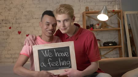 they : A happy international gay couple is sitting on the couch and holding a sign. We have feeling. Look at the camera. Home comfort on the background. 60 fps