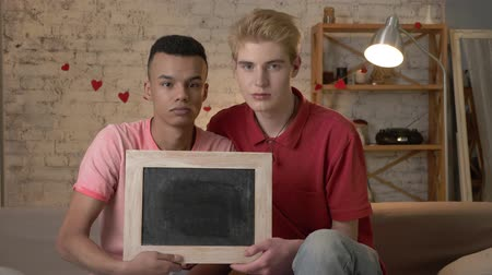 social inequality : A sad international gay couple is sitting on the couch and holding a empty sign. Home comfort on the background. 60 fps