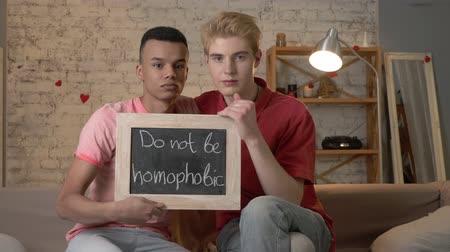 they : A sad international gay couple is sitting on the couch and holding a sign. Do not be homophobic. Look at the camera. Home comfort on the background. 60 fps