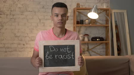 hatred : A sad African guy sits on the couch and holds a sign. Do not be racist. Anti-racism, national inequality concept. Look at the camera. 60 fps Stock Footage