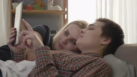 two gender : Lesbian couple is resting on the couch, using tablet computer, scrolling photos on tablet, smiling, family idyll, love, cute, close up 60 fps Stock Footage