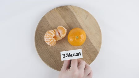 mandarinka : Amount of calories in Mandarin, male hand puts a plate with the number of calories on a Mandarin, top shot Dostupné videozáznamy