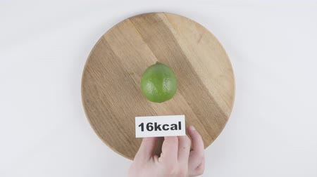 lyme : Amount of calories in lime, male hand puts a plate with the number of calories on a lime, top shot 60 fps Stock Footage