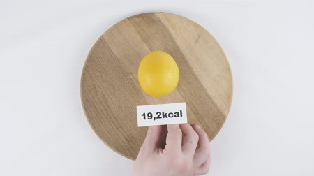 limon : Amount of calories lemon, male hand puts a plate with the number of calories on a lemon, top shot 60 fps