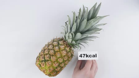 capsicum : Amount of calories in pineapple, male hand puts a plate with the number of calories on a pineapple, top shot 60 fps