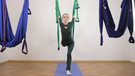 gravity : Young caucasian woman making antigravity fly yoga exercises in hammock in studio indoors. Aerial aero fly fitness trainer workout. High Lunge. Meditates, harmony and serenity concept 60 fps