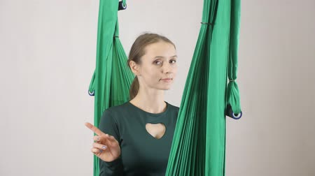 hamak : Young woman sits on a hammock and Saying no By Shaking Head. Aerial aero fly fitness trainer workout. Meditates, harmony and serenity concept, 60 fps