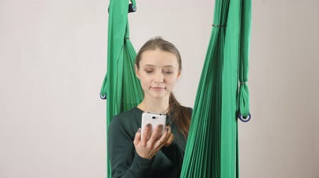 hamak : Young woman sits on a hammock and answers a phone call, smartphone. Aerial aero fly fitness trainer workout. Meditates, harmony and serenity concept, 60 fps