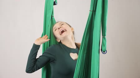 stay active : Young woman sits on a hammock smiling stretch out hands and yawing. Aerial aero fly fitness trainer workout. Meditates, harmony and serenity concept, 60 fps Stock Footage