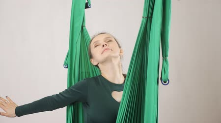 stay active : Young woman sits on a hammock smiling stretch out hands. Aerial aero fly fitness trainer workout. Meditates, harmony and serenity concept, 60 fps