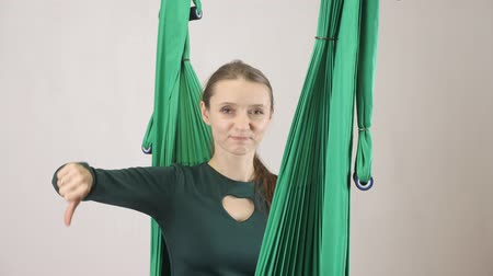 displeasure : Young woman sits on a hammock smiling showing dislike sign. Aerial aero fly fitness trainer workout. Meditates, harmony and serenity concept, 60 fps